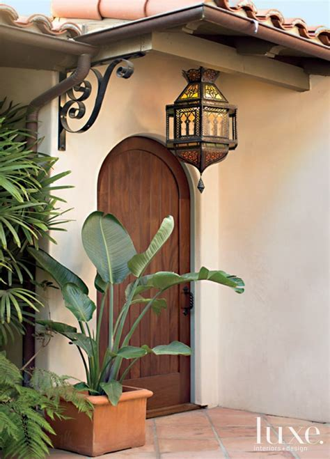 brown mediterranean style arched front door luxe