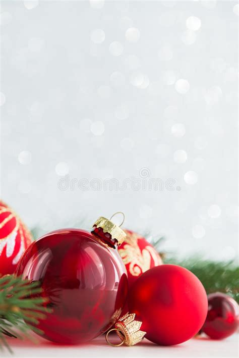 red ornaments and xmas tree on glitter holiday background