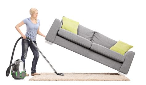 Woman Picking Up Couch And Vacuuming Under With Top