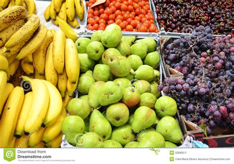 Fruit Stand At The Market With Bananas Pears Grapes And