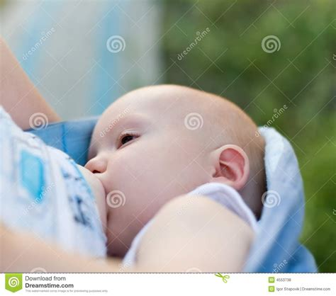 Mother Breast Feeding Her Infant In Sling Royalty Free