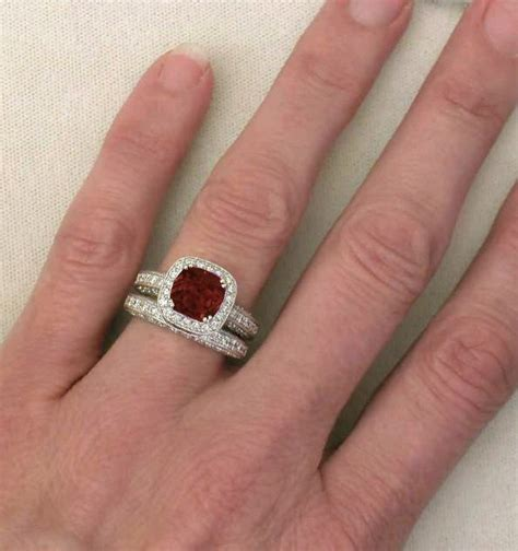 cushion cut garnet and diamond halo engagement ring and wedding band with milgrain edging and