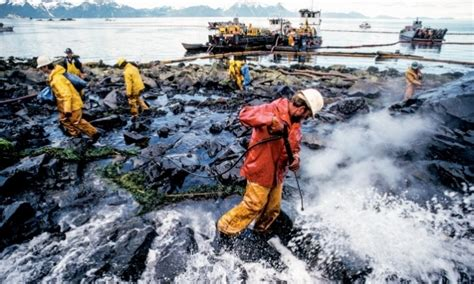 Workers Spray Oilcovered Rocks On The Shore Of An Alaskan