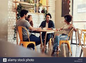 Young people sitting at a cafe table. Group of friends ...