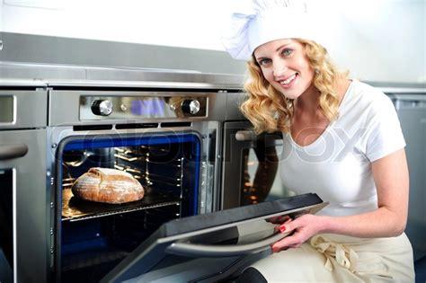 pretty baker opening  oven door stock photo colourbox