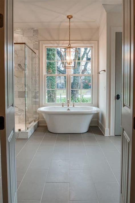 gray porcelain tile bathroom brass lantern over tub and gray porcelain floor tiles transitional bathroom