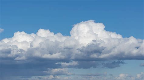 Timelapse Of Big White Fluffy Clouds Over A Blue Sky. 4k