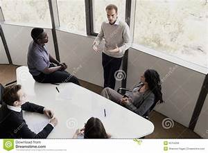 Five Business People Sitting At A Conference Table And ...