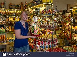 Young Woman Holding A Giant Matryoshka Doll For Sale In A
