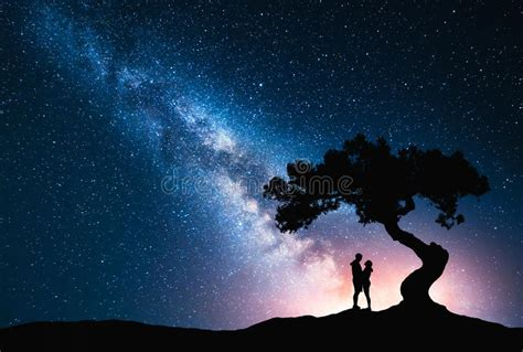 Milky Way With Hugging Couple Under The Tree Stock Photo