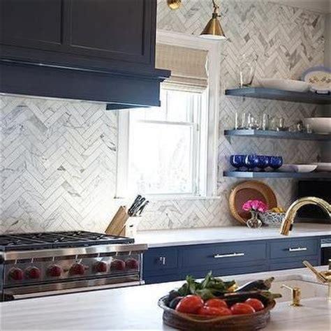 navy blue kitchen cabinets  brass bar pulls  marble