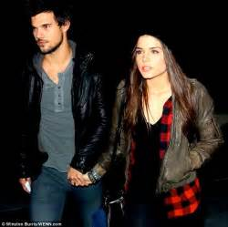 Taylor Lautner and girlfriend Marie Avgeropoulos hold ...