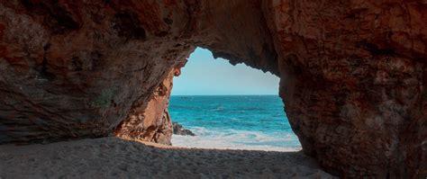 Download wallpaper 2560x1080 beach, rock, cave, sea, sand ...