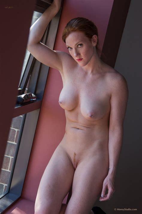 Redhead Babe Likes Posing Naked Next To The Window Photos