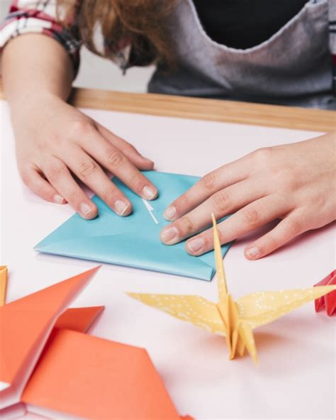 close   woman hand folding origami paper  making