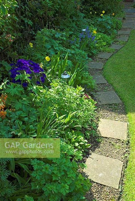 curved garden path gap gardens curved garden path with stone slabs and gravel edging a spring border with lights