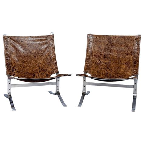 pair of mid century modern sling chairs in distressed