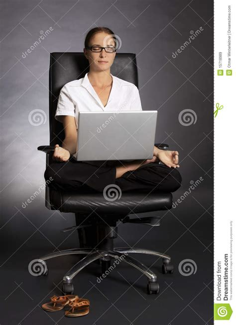 in lotus pose in chair with laptop royalty free
