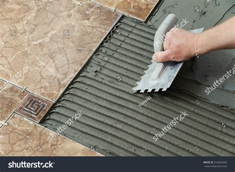 laying ceramic tiles troweling adhesive onto stock photo