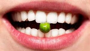 Female Smile With Pea Between Teeh In A Mouth