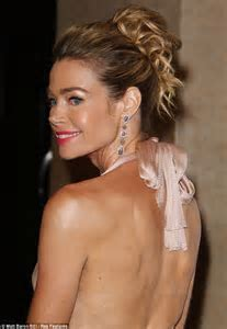 Denise Richards exudes glamour in low cut champagne gown