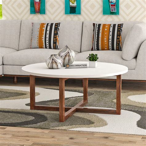 Its rectangular tabletop sits on a classic trestle base with carved wooden accents, and features a rustic look thanks to its visible wood grain and natural wood variation. Wooden MDF Round Coffee Table with Solid Wood Legs - White - FurnitureDekho
