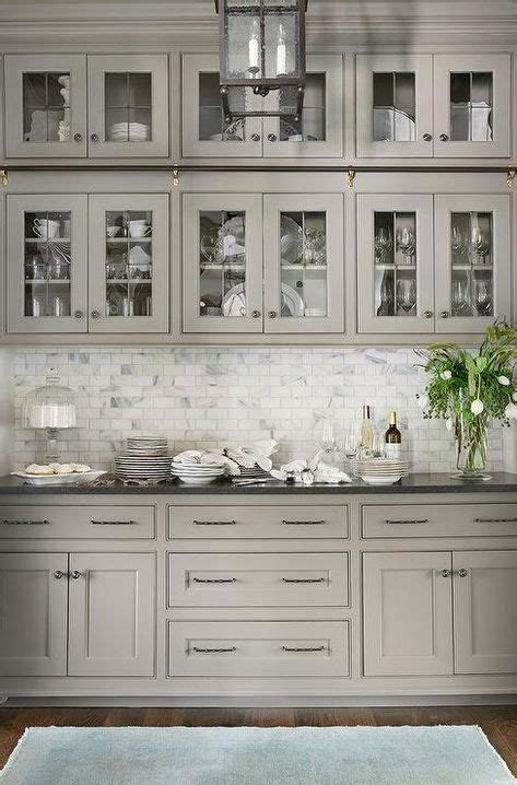 Light gray butler pantry features glass front cabinets
