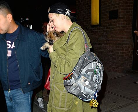 miley cyrus carries  infamous chanel graffiti backpack