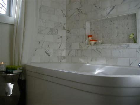 beautiful ensuite  west elm aluminum hexagon side table calcutta marble subway tile shower