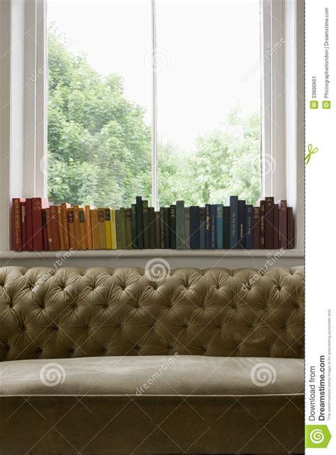 Play Windowsill by Row Of Books On Windowsill With Sofa In Foreground Stock