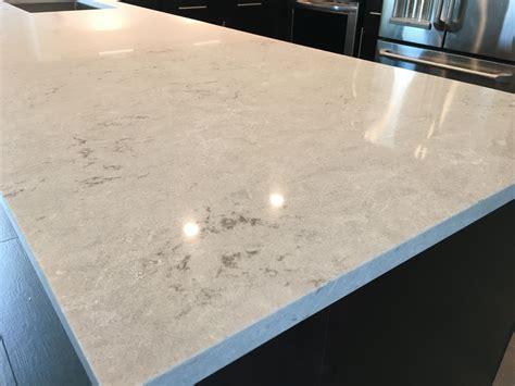 bianco drift caesarstone countertops  dark cabinets
