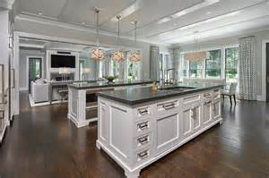 two kitchen islands side by side white kitchen islands with honed black marble countertops transitional kitchen