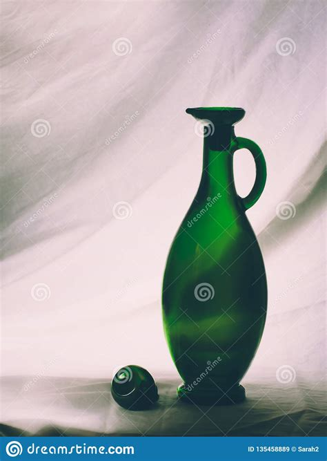 Olive oil bottle banner template, glass blank flask floating in liquid green flow with leaves and berries. Vintage Green Glass Olive Oil Bottle, Backlit. Light ...
