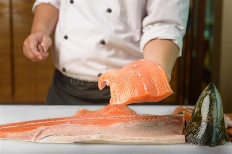 Chef Preparing A Fresh Salmon Fish On A Cutting Board