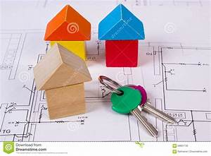 Houses Of Wooden Blocks And Keys On Construction Drawing