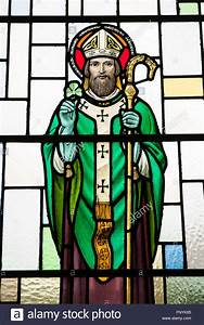 A stained glass window of Saint Patrick, holding a ...