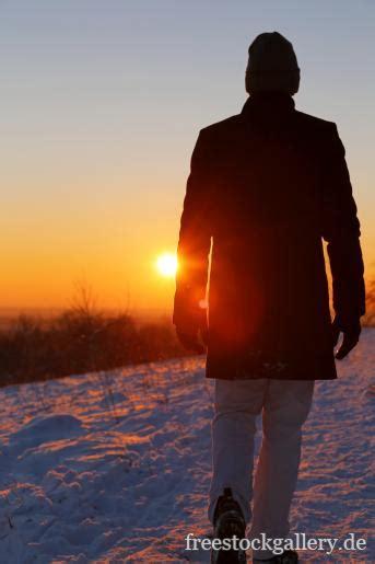 mann geht im schnee spazieren sonnenuntergang