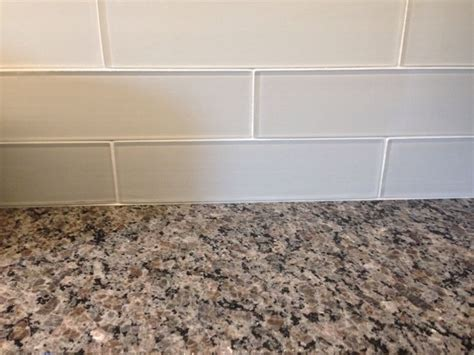 new caledonia granite countertops and white glass tile