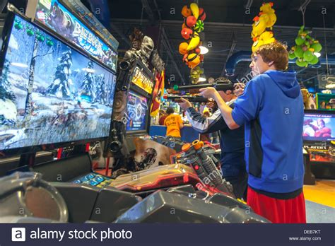 Two Young Men Playing Video Shooting Games With Guns In An