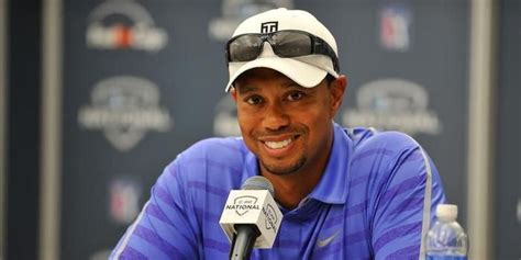 Tiger Woods Wearing a blue shirt, white hat and sunglasses ...