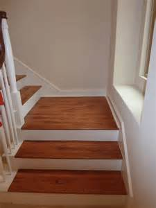 brown color vinyl wood plank flooring on stairs with wall and wood railings painted with white