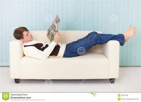 sofa mit einer armlehne name mann liegt bequem auf sofa mit einer zeitschrift stockfoto