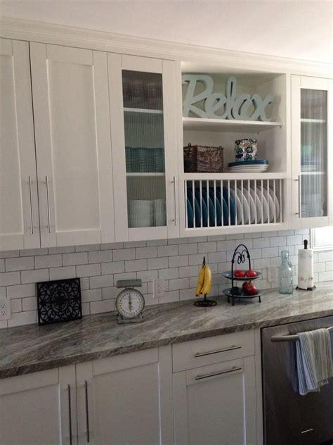 white shaker cabinets  glass doors open shelves plate rack granite counters kitchen