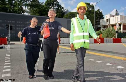 construction worker helps blind cross  road