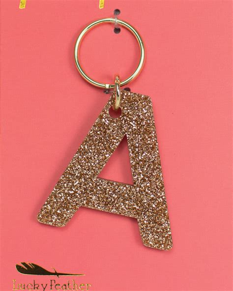 lucky feather glitter letter keychain belle  llc