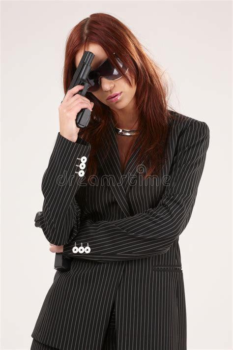 mooie vrouw in zwarte met kanon grijs stock