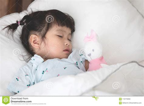 Cute Little Asian Girl Sleeping With Doll In Bed Stock