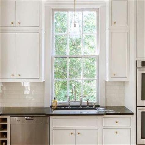 white kitchen cabinets  brass hardware  black