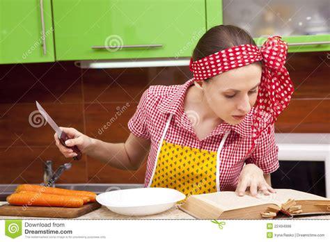 femme cuisine femme dans la cuisine avec le livre de recette de couteau