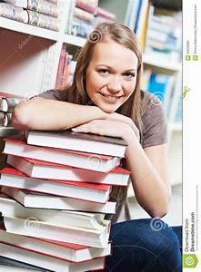 Smiling Young Adult Woman Reading Book In Library Royalty ...